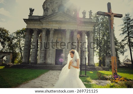 Beautiful young bride wearing wedding dress and posing next to old church.  - stock photo