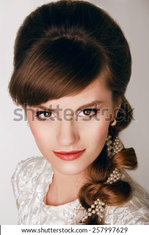 Beautiful young bride with retro hairstyle smiling happily - stock photo