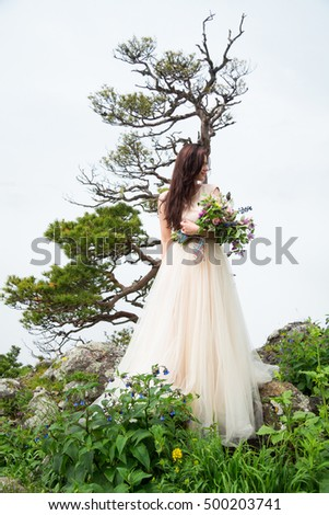 Beautiful young bride with wedding bouquet posing near rocks against background the mountains