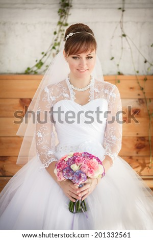Beautiful young bride with wedding makeup and hairstyle, attractive newlywed woman wedding flowers. Happy Bride waiting groom. Marriage Wedding day moment. Bride portrait. soft tonality