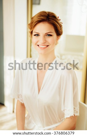Beautiful young bride with wedding makeup and hairstyle in bedroom, newlywed woman final preparation for wedding. Happy Bride waiting groom. Marriage Wedding day moment. Bride portrait soft focus - stock photo