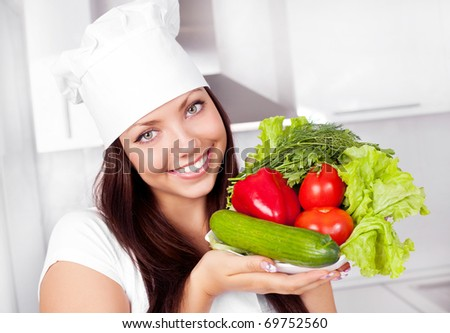 beautiful young brunete woman with vegetables in the kitchen - stock photo