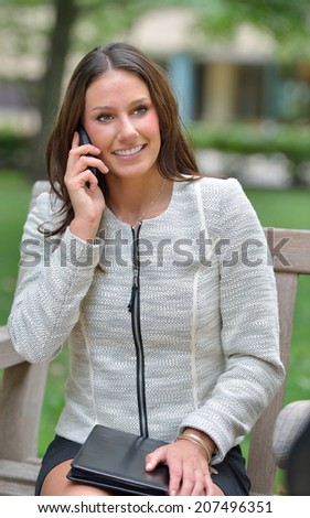 Beautiful young brunette business woman in park - sitting on bench talking on cell phone - stock photo