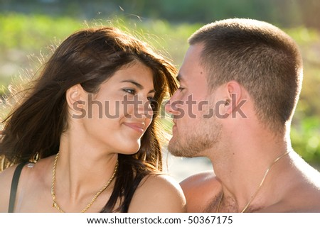 Beautiful young brunette couple smiling at each other at the beach