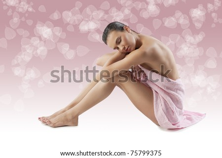 beautiful young brunette covering her naked body with a pink bath towel sitting down on white floor - stock photo