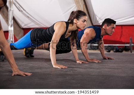 Beautiful young brunette doing some push ups with some other people at a gym - stock photo