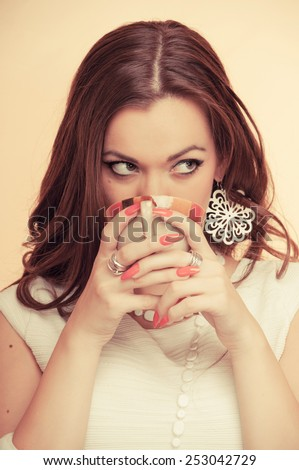 Beautiful young brunette drinking coffee, on beige background - stock photo