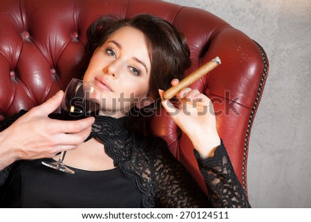 Beautiful young  brunette enjoy her glass of red wine - man's hand - stock photo
