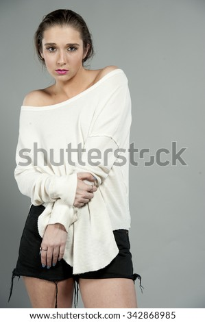 Beautiful young brunette female wearing a white top with slicked back hair, on a gray studio background.