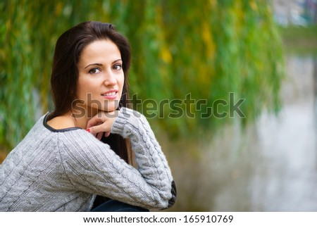 Beautiful young brunette girl at autumn park
