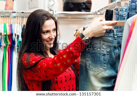 Beautiful young brunette girl choosing jeans in store - stock photo