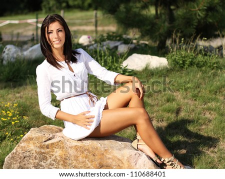 Beautiful young brunette girl in nature smiling