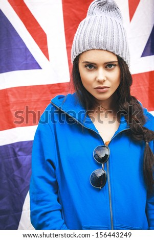 Beautiful young brunette girl in stylish clothes and sunglasses with national british flag in background. Outdoors, Lifestyle - stock photo