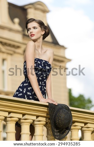 beautiful young brunette girl posing like vintage diva on balcony of ancient palace with elegant hair-style, red lipstick, short dress and hat in the hand  - stock photo