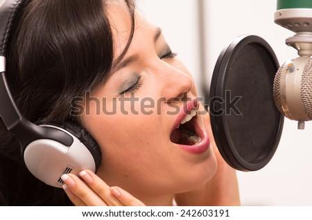 beautiful young brunette girl singing in music studio - stock photo
