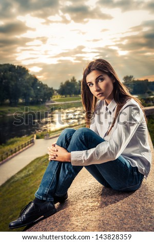 Beautiful young brunette girl sitting outdoors near the river