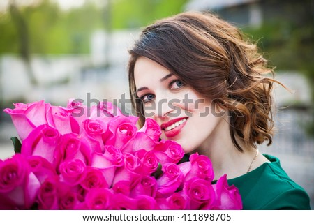Beautiful young brunette girl with Blue Eyes and healthy curly Hair smelling flowers holding pink roses bouquet. Perfect skin and makeup