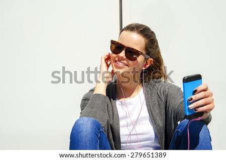 beautiful young brunette hair hipster woman listening music earphones in the city