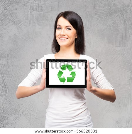 Beautiful, young brunette holding a tablet over isolated background. Recycling concept. - stock photo