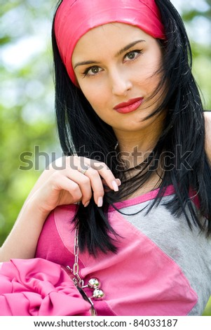 Beautiful young brunette holding pink purse