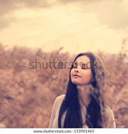 beautiful young brunette in a field enjoying the freshness of spring - stock photo