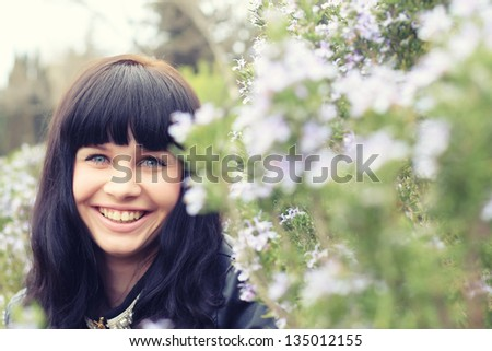 beautiful young brunette in a grass field of rosemary - stock photo