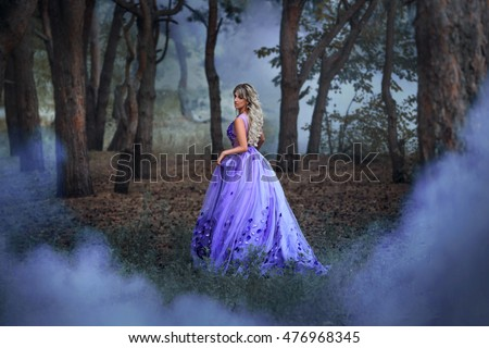Beautiful, young, brunette in a luxurious, purple, long dress.  Fairy Photo. Creative toning. Queen walks through the forest. Garden shrouded in mist background.