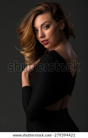 Beautiful young brunette in a tight black dress - stock photo