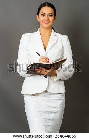 beautiful young brunette in a white business suit on a gray background - stock photo