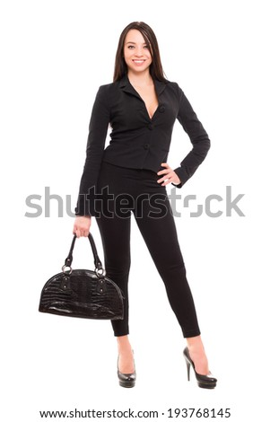 Beautiful young brunette in black clothes with handbag. Isolated on white - stock photo