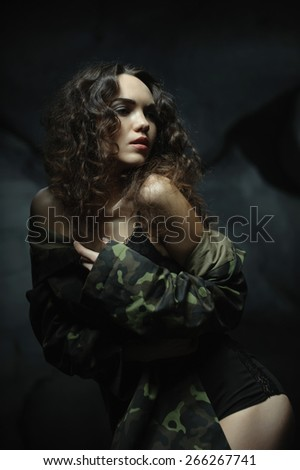 beautiful young brunette in military clothing. posing for the camera. Grey stones in the background - stock photo