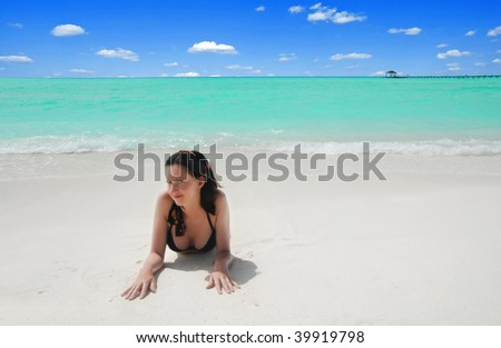 Beautiful young brunette is laying near the tropical sea on the white beach.