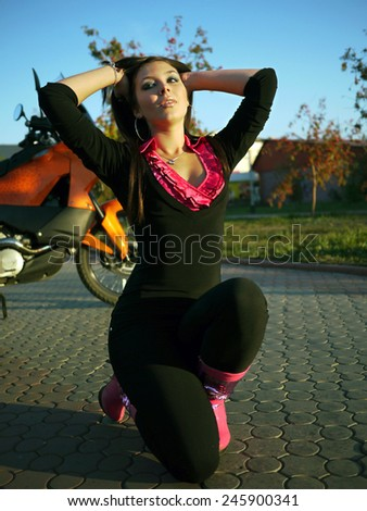Beautiful young brunette on a motorcycle. - stock photo