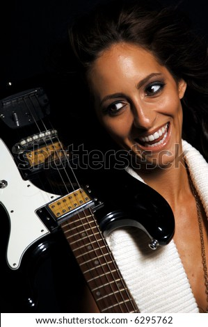 Beautiful young brunette over black in a low cut white knit sweater with an electric guitar