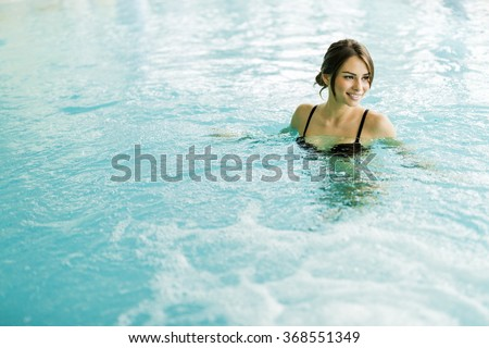 Beautiful young brunette relaxing happily  in a swimming pool - stock photo