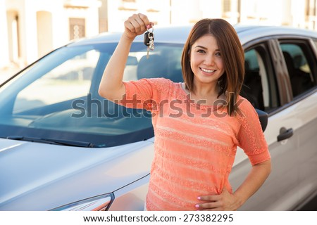 Beautiful young brunette showing off the keys for her brand new car and smiling - stock photo