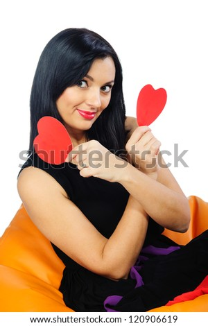 Beautiful young brunette sitting on orange couch with two red Valentine hearts. Isolated on white background. - stock photo