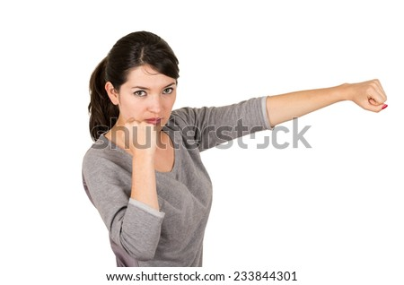 Beautiful young brunette strong confident girl posing punching to the side fighting position isolated on white - stock photo