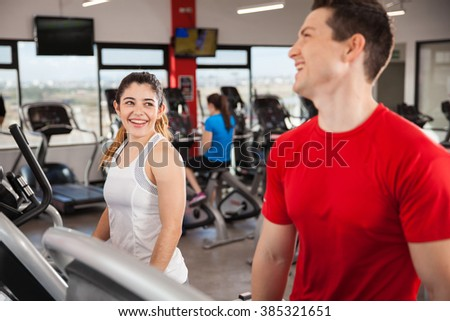 Beautiful young brunette talking and laughing with a young man while both do some cardio
