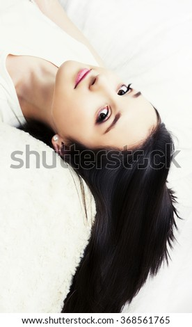 beautiful young brunette teenage girl   with long dark hair in bed on white linen - stock photo