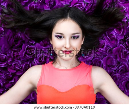 beautiful young brunette teenage girl   with makeup and flying long hair in the studio - stock photo