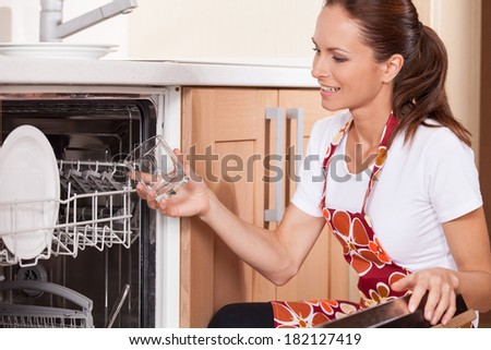 Beautiful young brunette washing dishes. attractive housewife taking dishes from dishwasher - stock photo