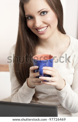 Beautiful young brunette with a cup of tea - stock photo