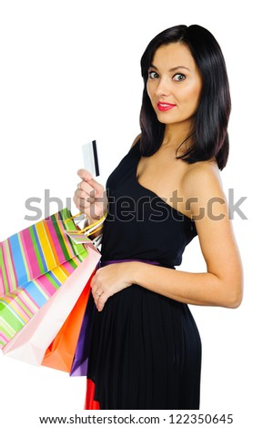 Beautiful young brunette with credit card and shopping bags isolated on white background