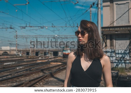 Beautiful young brunette with long hair posing along railroad tracks - stock photo