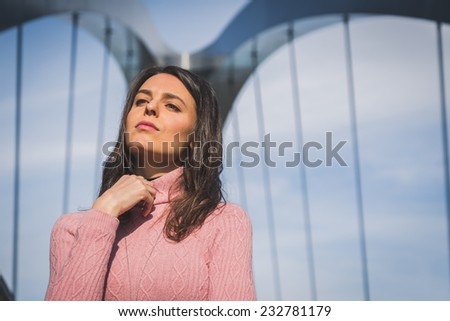 Beautiful young brunette with long hair posing on a bridge - stock photo