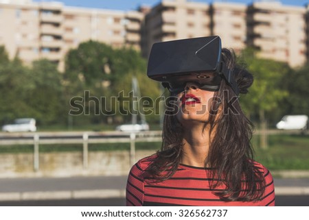 Beautiful young brunette with long hair wearing virtual reality headset in an urban context