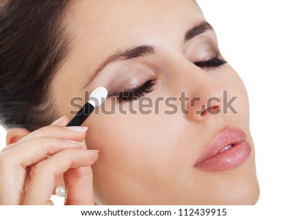Beautiful young brunette woman applying eye shadow from a small portable compact set of colours isolated on white - stock photo