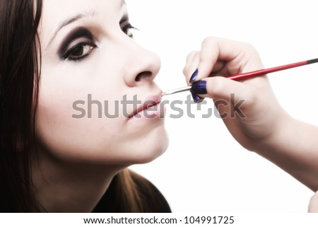 beautiful young brunette woman applying lips make-up zone isolated background - stock photo
