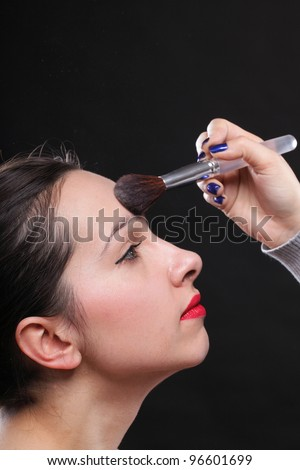 beautiful young brunette woman applying powder with a brush black background